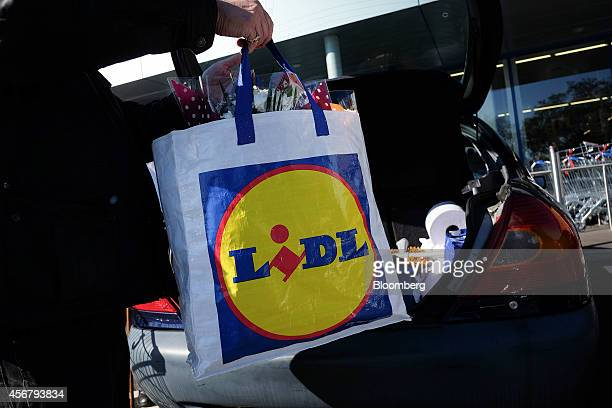 A shopper loads a Lidl branded shopping bag in to the truck of his automobile outside a Lidl discount supermarket operated by Lidl Ltd in the Catford...