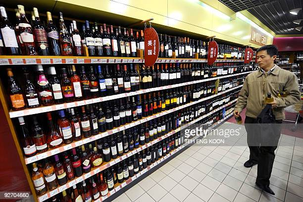 A shopper look at US made red wine at a Carrefour hypermarket in Beijing on February 21 2008 With millions of consumers at stake global retail giants...