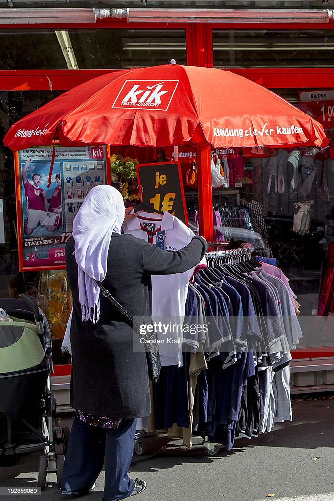 A shopper looks among clothes on display outside a Kik discount textiles store on September 18, 2012 in Berlin, Germany. Kik, a nationwide discount clothing chain in Germany, is reportedly among the companies that sourced some of its production to the garment factory in Karachi, Pakistan, that recently burned down, killing at least 258 people.