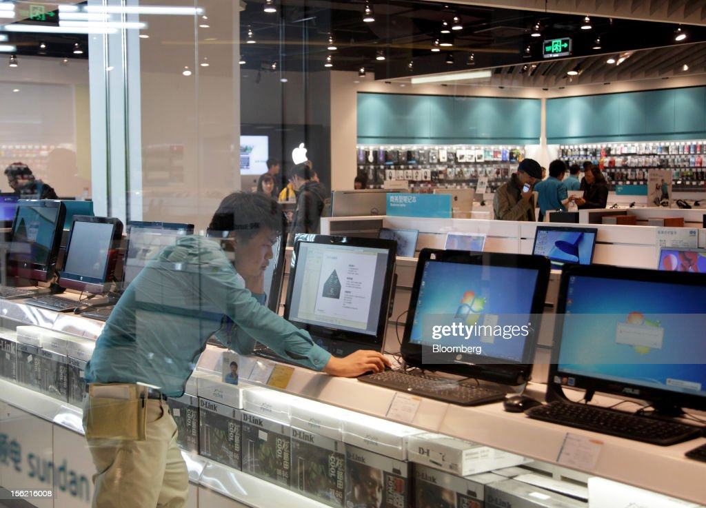 A shopper looks at a desk top computer at an electronics store in the Sanlitun area of Beijing, China, on Friday, Nov. 9, 2012. China's retail sales exceeded forecasts and inflation unexpectedly cooled to the slowest pace in 33 months, signaling the government is boosting growth without driving a rebound in prices. Photographer: Tomohiro Ohsumi/Bloomberg via Getty Images