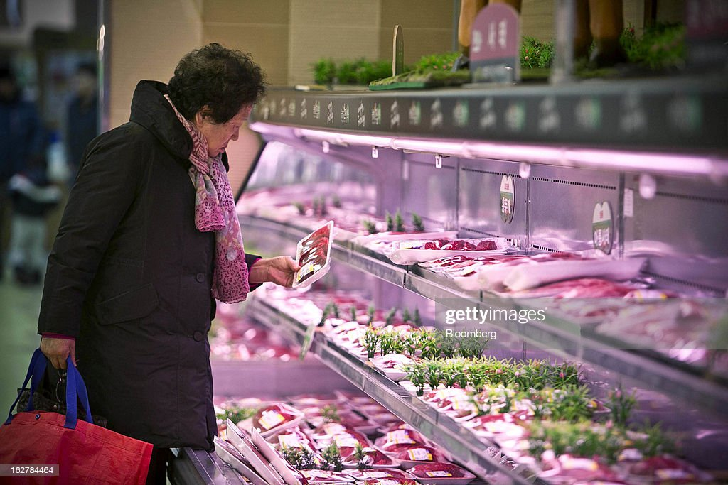 A shopper looks at a pack of meat at Hanaro Mart in Seoul, South Korea, on Tuesday, Feb. 26, 2013. South Korean consumer confidence remained at its highest level since May as gains in the won drove down the prices of imported goods. Photographer: Jean Chung/Bloomberg via Getty Images
