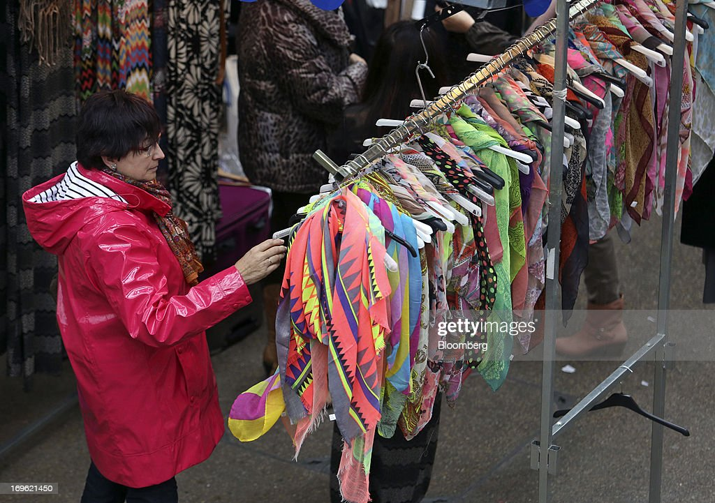A shopper looks at brightly colored scarves displayed for sale at a stall inside Old Spitalfields Market in London, U.K., on Wednesday, May 29, 2013. Annual U.K. consumer-price inflation slowed to 2.4 percent last month from 2.8 percent in March, the Office for National Statistics said May 21. Photographer: Chris Ratcliffe/Bloomberg via Getty Images