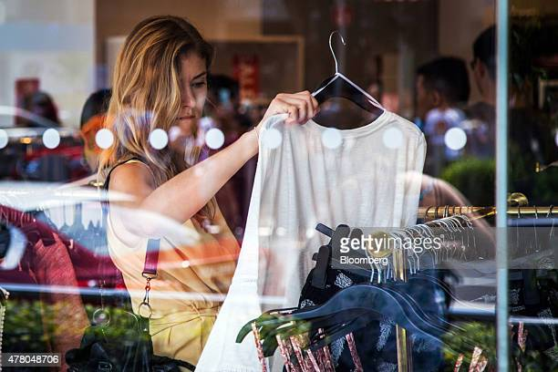 A shopper looks at clothing in a Hennes Mauritz AB store on Orchard Road in Singapore on Sunday June 21 2015 Consumer prices prices declined for a...