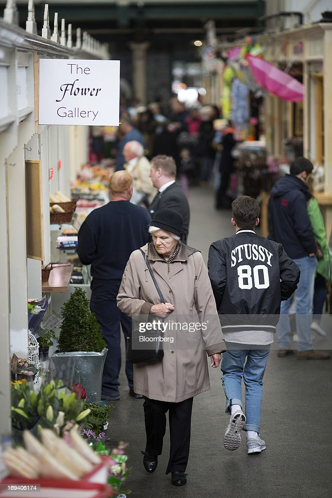 A shopper looks at flowers displayed for sale as she passes a stall at an indoor market in Cardiff, U.K. on Thursday, May 23, 2013. Bank of England Markets Director Paul Fisher said policy makers must continue to provide support to the British economy so that companies and consumers have room to reduce debts and rebuild confidence. Photographer: Simon Dawson/Bloomberg via Getty Images