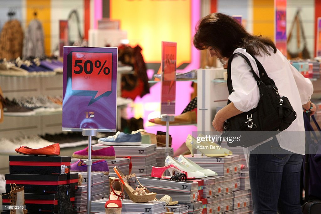 A shopper looks at shoes in a store advertising summer sales on August 1, 2012 in Berlin, Germany. German retailers began their annual summer clearance sale on Monday, offering deep discounts of up to 80 percent on warm weather items as they prepare to stock up for the autumn shopping season.