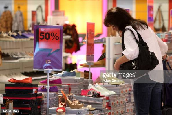 A shopper looks at shoes in a store advertising summer sales on August 1 2012 in Berlin Germany German retailers began their annual summer clearance...