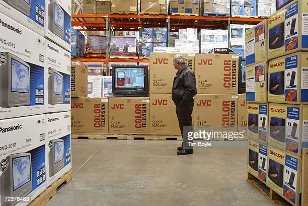 A shopper looks at televisions in the electronics department of a Costco Wholesale store March 8 2002 in Niles IL Warehouse retailer Costco Wholesale...