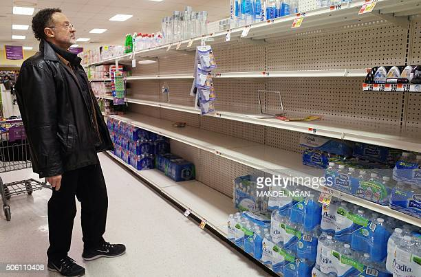 A shopper looks at the bottled water section at a supermarket on January 21 2016 ahead of an expected blizard in Washington DC A blizzard warning has...