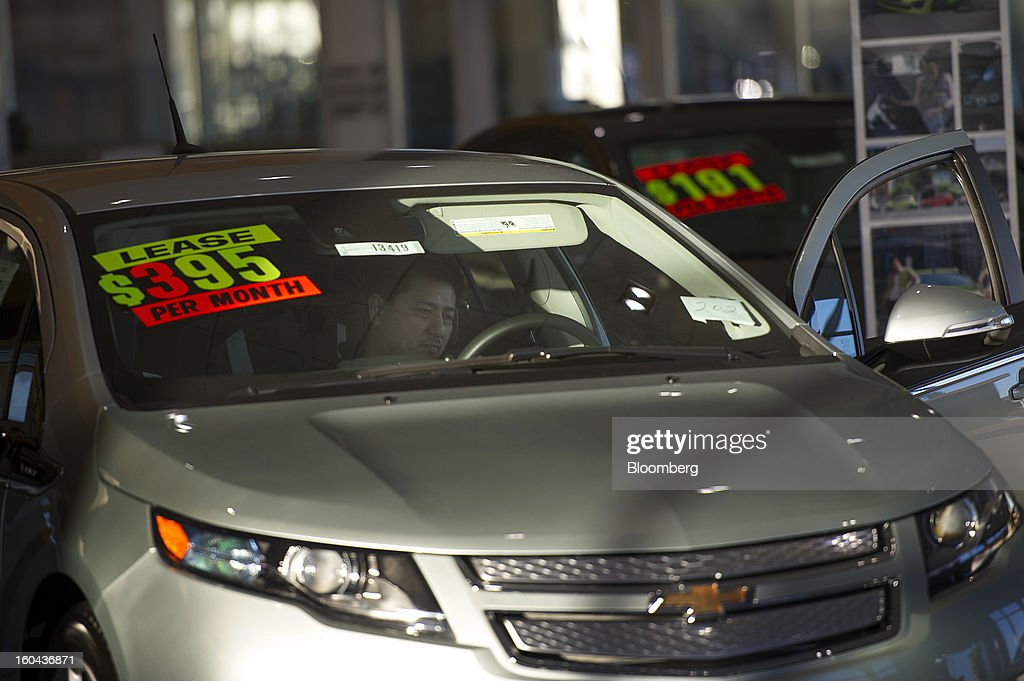 A shopper looks at the interior of a car at Stewart Chevrolet Cadillac dealership in Colma California US on Wednesday Jan 30 2013 US auto dealerships...
