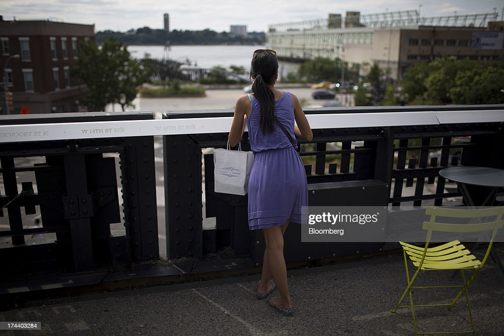 A shopper looks out towords the Hudson River on the High Line park in New York, U.S., on Wednesday, July 24, 2013. The U.S. Conference Board is scheduled to release consumer confidence figures on July 30. Photographer: Scott Eells/Bloomberg via Getty Images