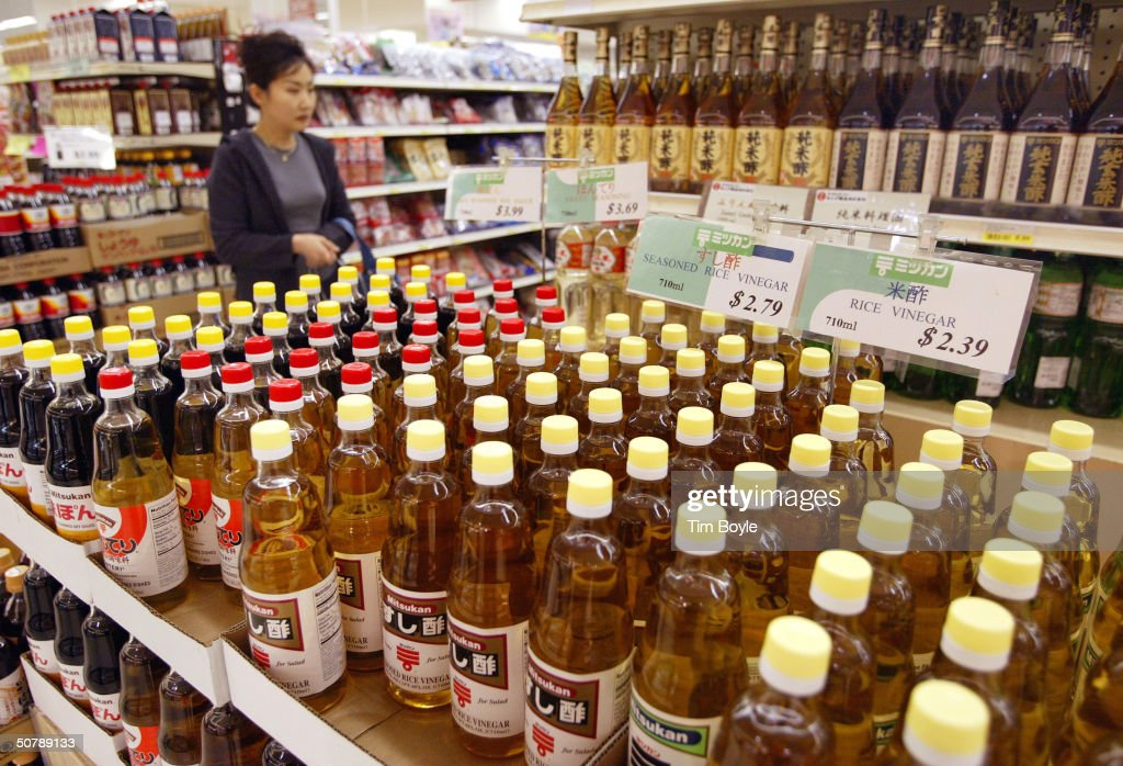 A shopper looks over bottles of rice vinegar at Mitsuwa Marketplace April 30 2004 in Arlington Heights Illinois For such reasons as health flavor and...