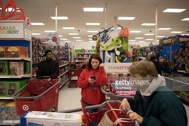 A shopper looks over her mobile phone at a Target Corp store ahead of Black Friday in Mentor Ohio US on Thursday Nov 27 2014 An estimated 140 million...