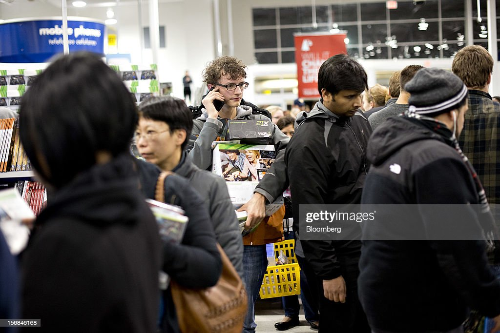 Shopper Lucas Geyer talks on his mobile phone as he waits to pay for merchandise at a Best Buy Co. store in Peoria, Illinois, U.S., on Friday, Nov. 23, 2012. Discount store shoppers are prepared to wait in long lines on Black Friday, though they are skeptical about whether they'll get the best deals of the season. Photographer: Daniel Acker/Bloomberg via Getty Images