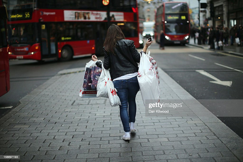 A shopper makes her way down Regent Street on December 24, 2012 in London, England. Many high street retailers have started their sales two days early this year on what is expected to be the busiest shooping day of the year.