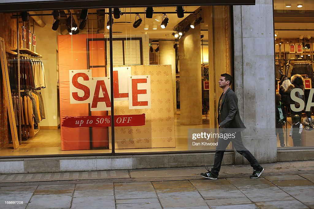 A shopper makes his way past sale signs in the window of a clothing store on Regent Street on December 24, 2012 in London, England. Many high street retailers have started their sales two days early this year on what is expected to be the busiest shooping day of the year.