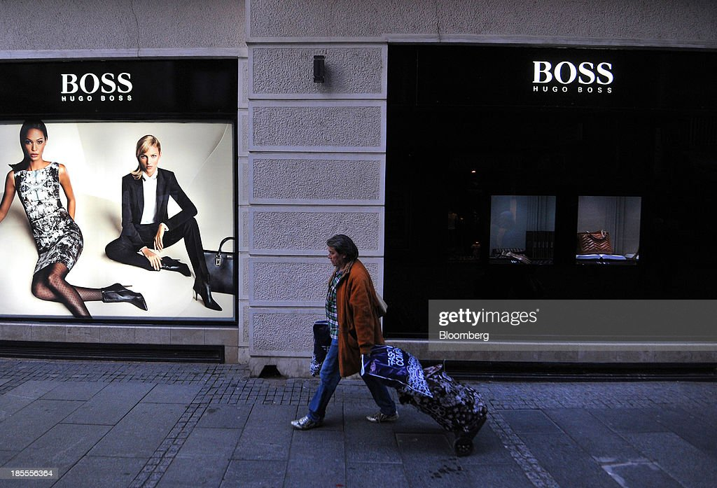A shopper passes a Hugo Boss AG fashion clothing store in Belgrade, Serbia, on Sunday, Oct. 20, 2013. Serbia's government revealed a salvo of measures to bring the public finance deficit and debt back under control by 2017 after the head of the largest coalition party warned the country was on the brink of insolvency. Photographer: Oliver Bunic/Bloomberg via Getty Images
