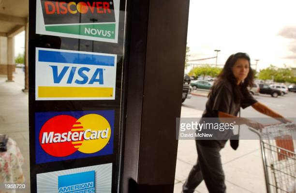 A shopper passes a shop door advertising acceptance of purchases with Master Card Visa and other credit cards April 29 2003 in Bakersfield California...