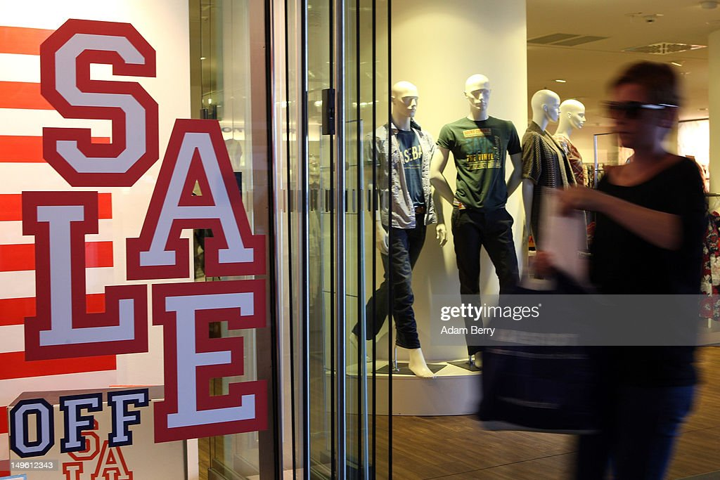 A shopper passes a store advertising summer sales on August 1, 2012 in Berlin, Germany. German retailers began their annual summer clearance sale on Monday, offering deep discounts of up to 80 percent on warm weather items as they prepare to stock up for the autumn shopping season.