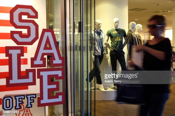 A shopper passes a store advertising summer sales on August 1 2012 in Berlin Germany German retailers began their annual summer clearance sale on...
