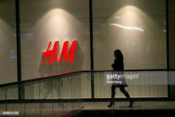 A shopper passes an illuminated HM logo in the window display of a Hennes Mauritz AB clothing fashion store inside the Mall of Berlin operated by...