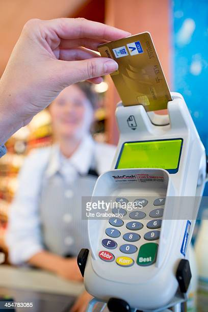 A shopper paying at the supermarket checkout with a debit card pictured on July 04 2013 in Bonn Germany