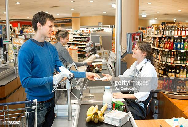 A shopper paying in cash at the supermarket checkout pictured on July 04 2013 in Bonn Germany