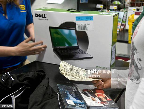 A shopper pays cash for a Dell computer and some DVDs at the Best Buy store in Corpus Christi Texas US on on Friday Nov 27 2009 Shoppers gathered at...