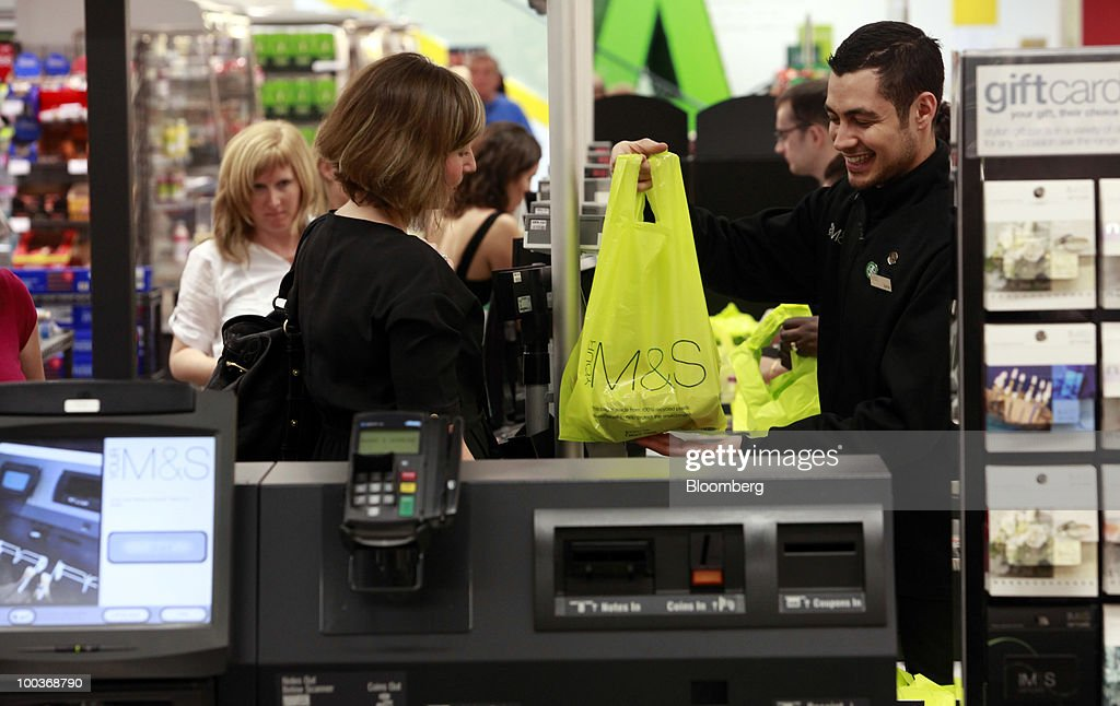 A shopper pays for purchases at a Marks & Spencer Group Plc (M&S) store in The Westfield Centre shopping mall in London, U.K., on Monday, May 24, 2010. The company, the U.K.'s biggest clothing retailer, reports its full-year earnings tomorrow. Photographer: Jason Alden/Bloomberg via Getty Images