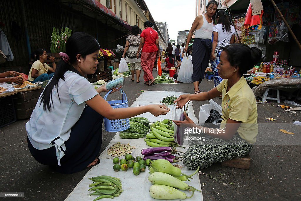 A shopper pays for vegetables at a market in downtown Yangon, Myanmar, on Sunday, Nov. 18, 2012. President Barack Obama will become the first sitting U.S. president to visit Myanmar when he travels to Yangon on Nov. 19 to meet President Thein Sein and Aung San Suu Kyi, the opposition leader who spent more than 15 years under house arrest before the country shifted to democracy after decades of military rule. Photographer: Dario Pignatelli/Bloomberg via Getty Images