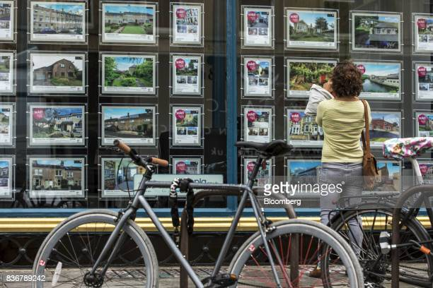 A shopper photographs an advert in the window of an estate agent in Bath UK on Monday Aug 21 2017 UK property prices stagnated in July as a slump in...