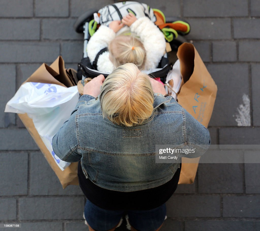 A shopper pushes a child in a pram with shopping bags balanced on its handles outside a shop on December 10, 2012 in Bristol, England. With internet shopping still on the rise, many traditional retailers claim this Christmas could be the one that will determine the future of the high street.