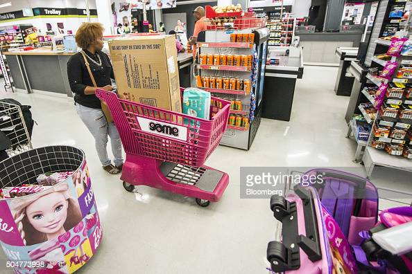A shopper pushes a shopping cart loaded with goods past the check out counters of a Game supermarket operated by Massmart Holdings Ltd at the...