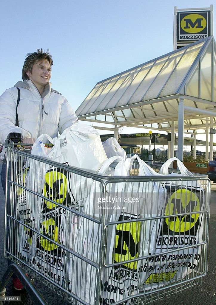 A shopper pushes her cart outside a Morrisons supermarket January 9, 2003 in London. The mid-size British supermarket chain, Morrisons, announced its bid to overtake rival Safeway in a 2.9 billion pound deal that would combine the firm with 589 stores and a 16 percent market share.