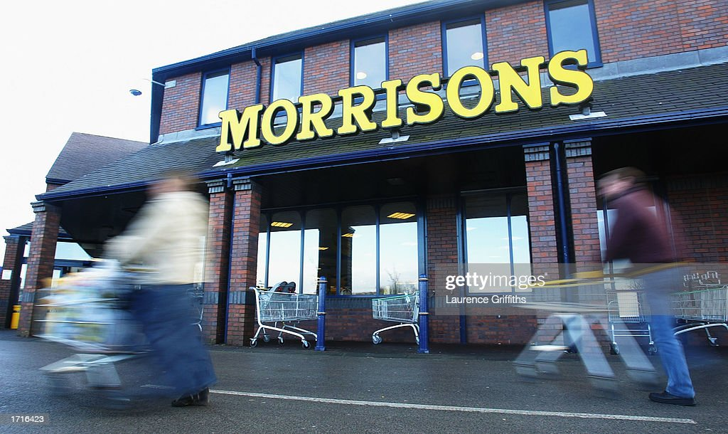 A shopper pushes her cart outside a Morrisons supermarket January 9, 2003 in Rochdale, Lancashire. The mid-size British supermarket chain, Morrisons, announced its bid to overtake rival Safeway in a 2.9 billion pound deal that would combine the firm with 589 stores and a 16 percent market share.