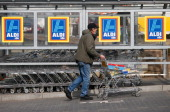 A shopper pushs a shopping cart outside an Aldi store on April 8 2013 in Ruesselsheim near Frankfurt Germany Aldi which today is among the world's...
