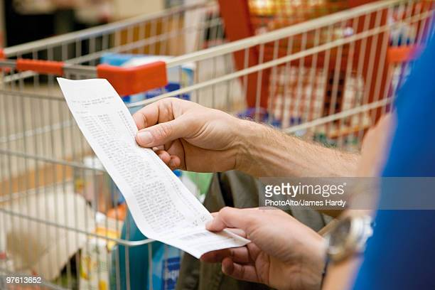 Shopper reviewing receipt, cropped