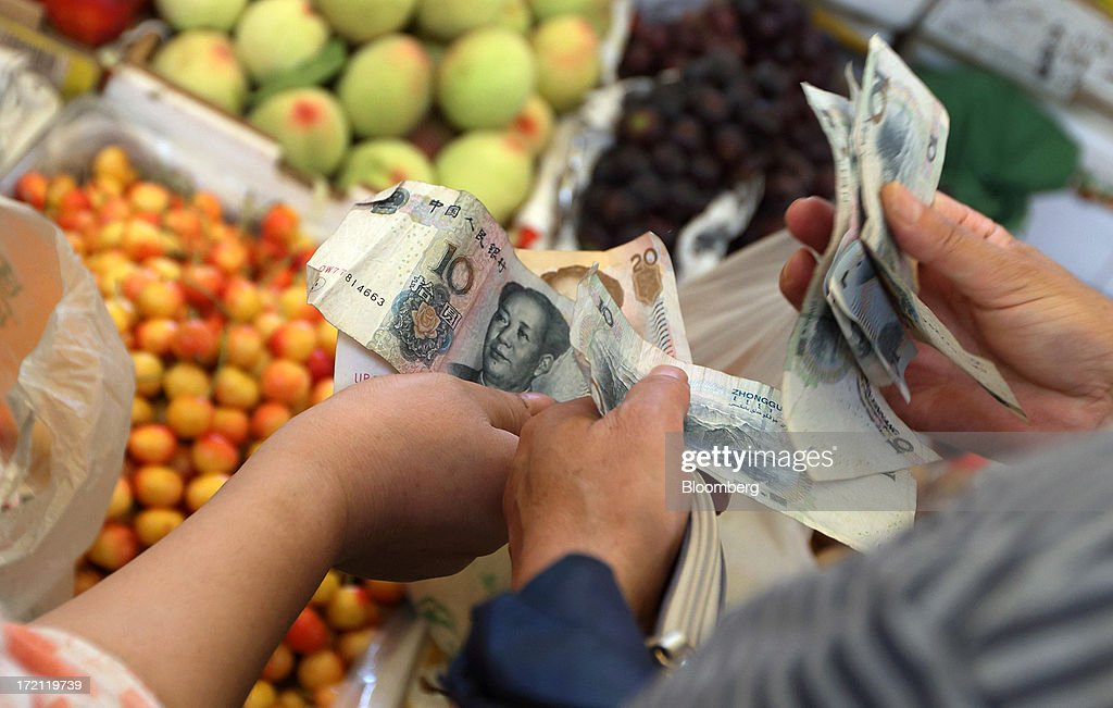A shopper, right, counts Chinese yuan banknotes as he shops for fruit and vegetables at a market in Shanghai, China, on Sunday, June 30, 2013. China's President Xi Jinping said officials shouldn't be judged solely on their record in boosting gross domestic product, the latest signal that policy makers are prepared to tolerate slower economic expansion. Photographer: Tomohiro Ohsumi/Bloomberg via Getty Images