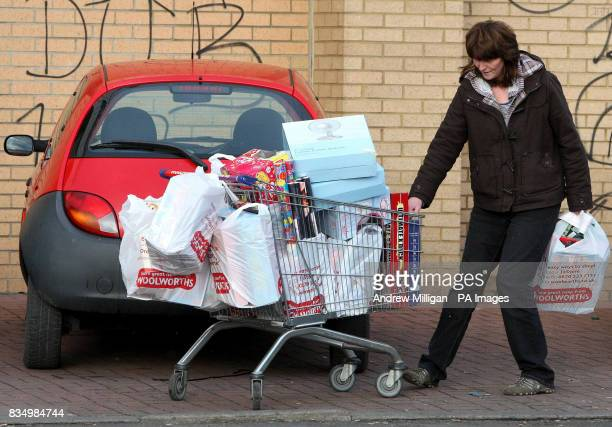 Shopper Sandra Melville takes her trolley to her car after buying discounted items at a Woolworths store in Edinburgh before it closes for the final...