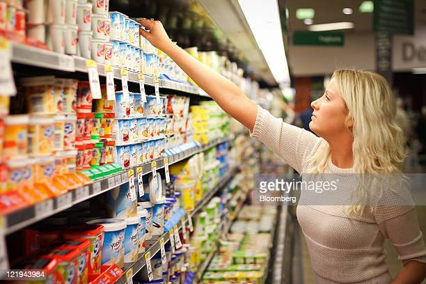 A shopper selects yoghurt at a Woolworths Ltd supermarket in Sydney Australia on Wednesday Aug 24 2011 Woolworths Ltd Australia's biggest retailer is...