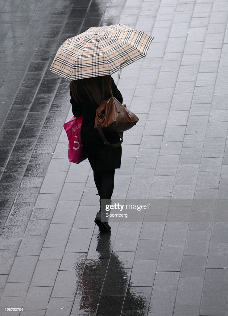 A shopper shelters from the rain beneath a Burberry-print umbrella as she leaves the Westfield Stratford City shopping mall in London, U.K., on Thursday, Dec. 27, 2012. Overall Christmas shopping in the U.K. was similar to last year, according to the British Retail Consortium. Photographer: Chris Ratcliffe/Bloomberg via Getty Images