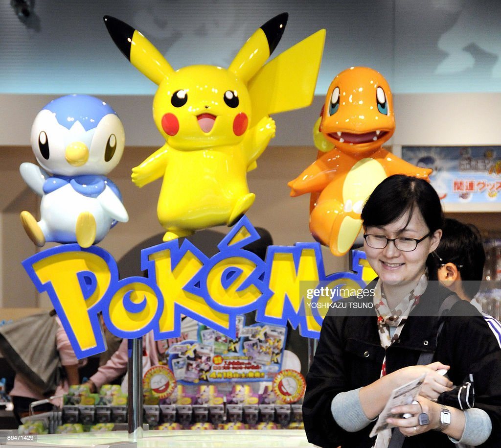 A shopper smiles as she stands in front of a display featuring the computer game character Pokemon, at a shop in Tokyo on May 7, 2009. Nintendo bucked the economic gloom with record profits for the year to March, saying the video game industry was proving to be relatively recession-proof. The strong results are in stark contrast to the financial woes of most of Japan's electronics giants, which have been badly hurt by the economic crisis. AFP PHOTO / Yoshikazu TSUNO