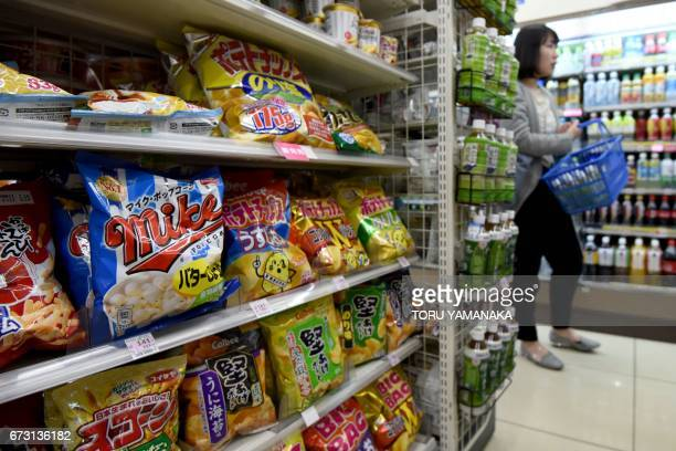 A shopper stands beside shelves with packets of potato chips at a convenience store in Tokyo on April 26 2017 Japan is in the midst of a dire crisps...