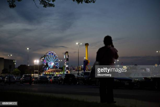 A shopper stands near the Dreamland Amusements carnival in the parking lot of the Marley Station Mall in Glen Burnie Maryland US on Friday April 28...