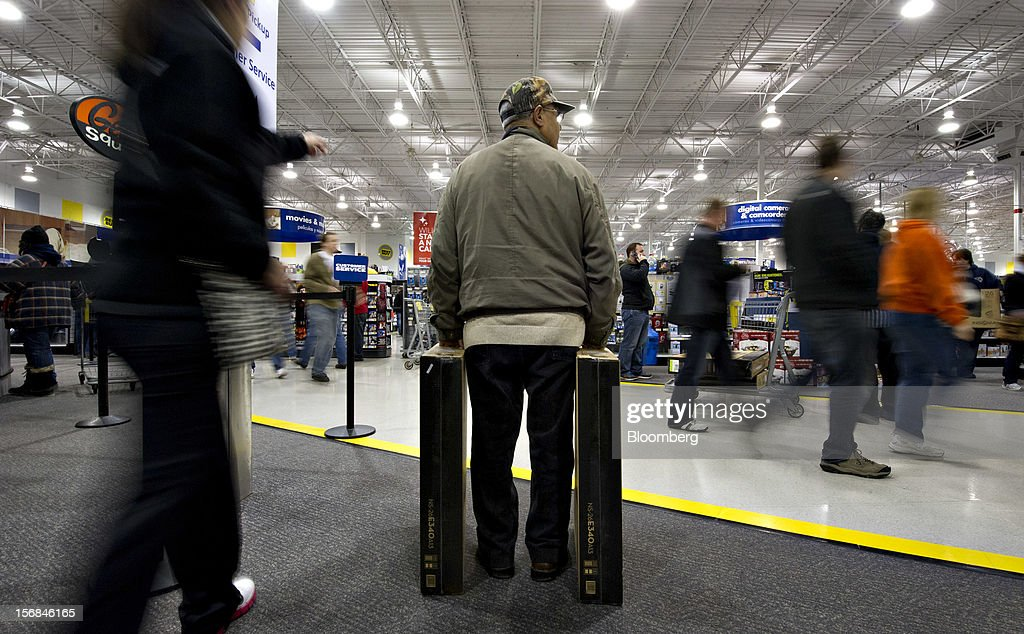 A shopper stands with two flat screen televisions at a Best Buy Co. store in Peoria, Illinois, U.S., on Friday, Nov. 23, 2012. Discount store shoppers are prepared to wait in long lines on Black Friday, though they are skeptical about whether they'll get the best deals of the season. Photographer: Daniel Acker/Bloomberg via Getty Images