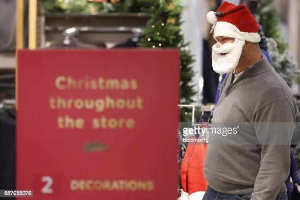 A shopper tries on a Father Christmas hat and beard inside a branch of Marks Spencer Group Plc in London UK on Tuesday Dec 5 2017 Brexit uncertainty...