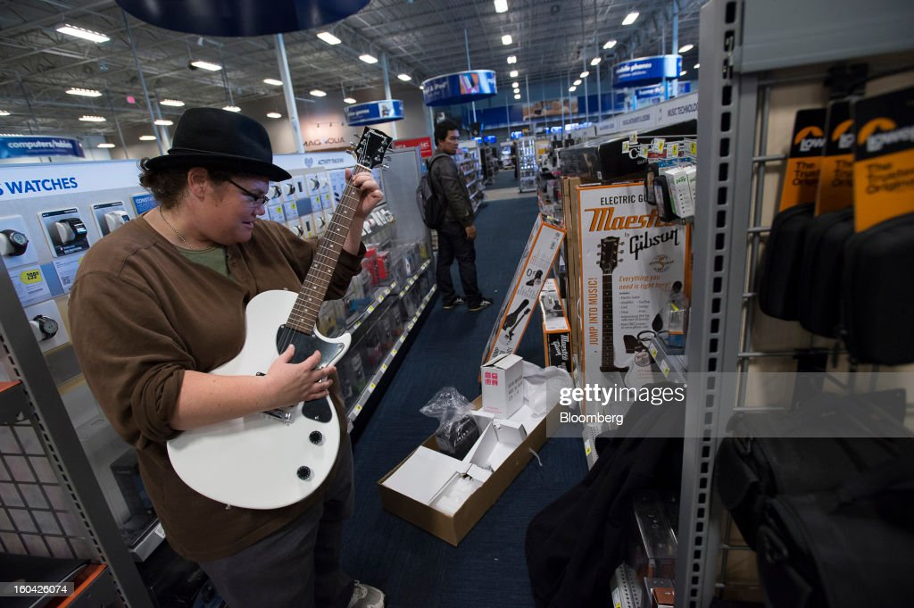 A shopper tries out a guitar at a Best Buy Co. store in San Francisco, California, U.S. on Wednesday, Jan. 30, 2013. Consumer spending in the U.S. climbed in December as incomes grew by the most in eight years, a sign the biggest part of the economy was contributing to the expansion as the year drew to a close. Photographer: David Paul Morris/Bloomberg via Getty Images