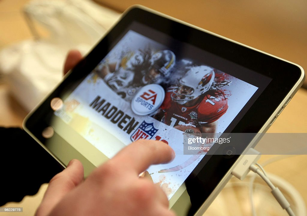A shopper tries out a Madden NFL video game on an iPad at Apple Inc.'s flagship store on Fifth Avenue in New York, U.S., on Saturday, April 3, 2010. With the iPad, Apple bets it can succeed where rivals such as Microsoft Corp. failed: building a following for a device that's bigger than a mobile phone, yet has fewer features than a laptop. Photographer: Jin Lee/Bloomberg via Getty Images