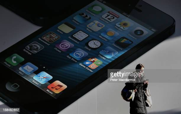 A shopper uses a mobile phone next to a giant advertisment for the Apple iPhone 5 near Oxford Street on December 17 2012 in London England Thousands...