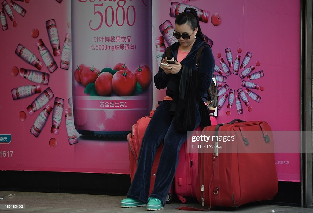 A shopper uses her phone in a commercial district of Shanghai on October 18, 2013. China's economy expanded 7.8 percent year-on-year in July-September, data showed, snapping two quarters of slowing growth, but analysts questioned whether the improvement was sustainable. AFP PHOTO/Peter PARKS