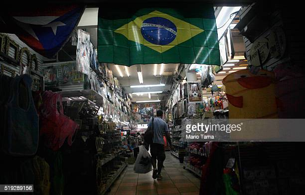 A shopper walks beneath a Brazilian flag in the Saara discount shopping district on April 5 2016 in Rio de Janeiro Brazil Brazil is in the midst of...